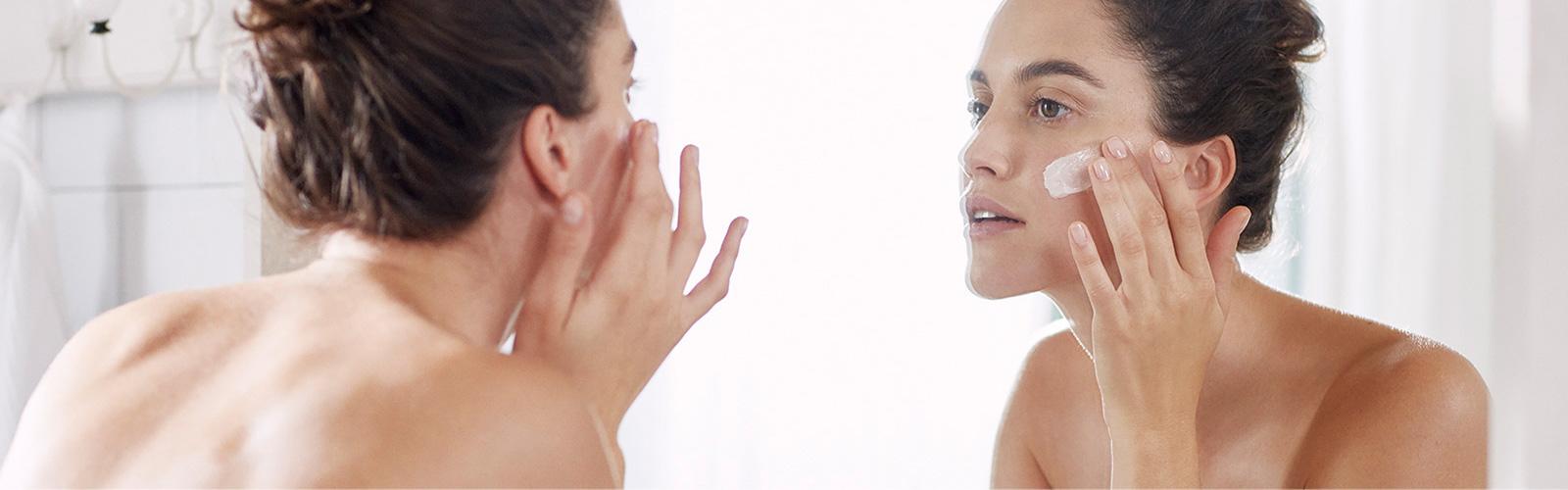 Eine Frau, die ihr Gesicht mit Feuchtigkeit versorgt